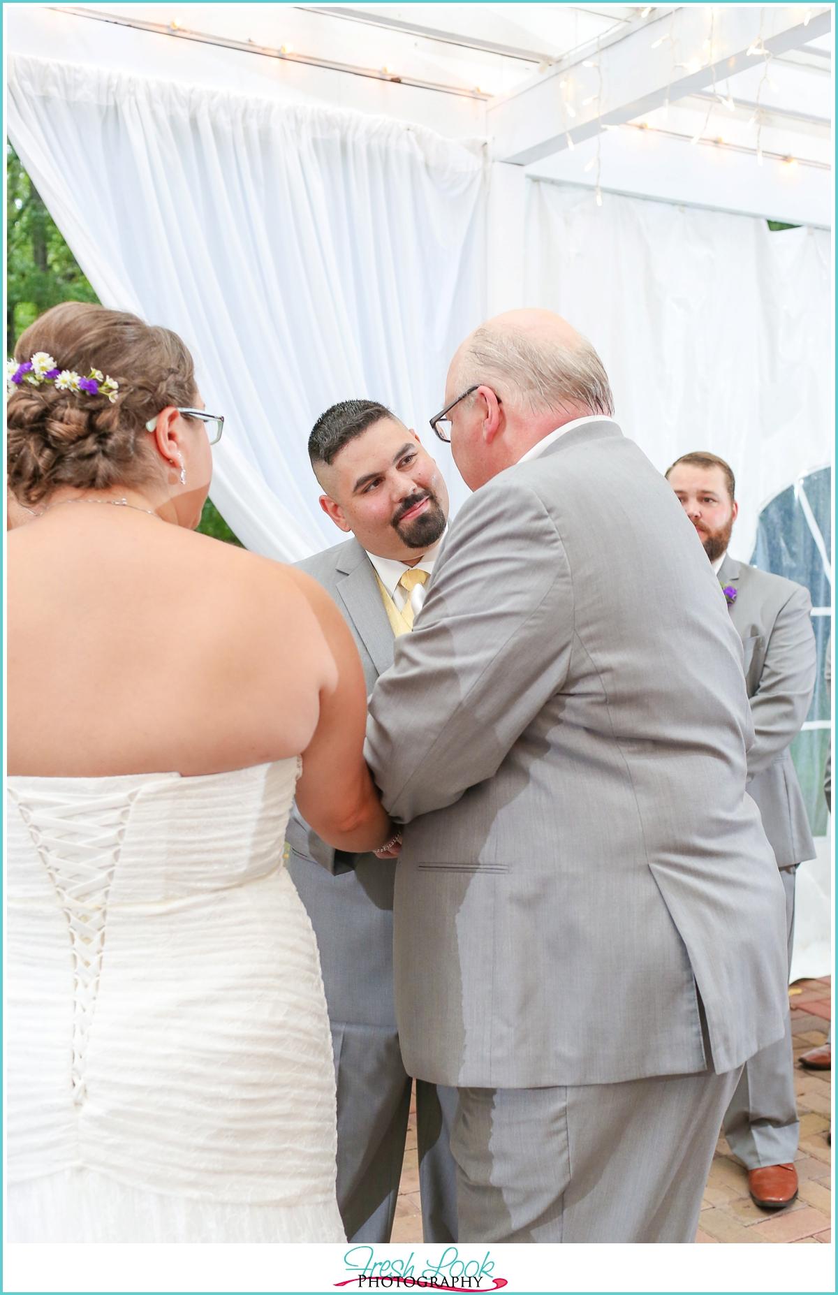 handing the bride to her groom